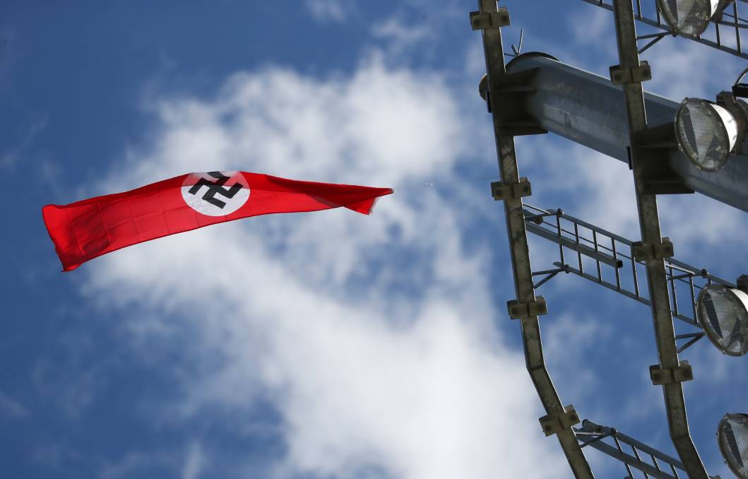 OFFENSIVE ACT: A Nazi flag is seen flying from the top of a light tower at Robertson Oval on Monday afternoon. Picture: Emma Hillier